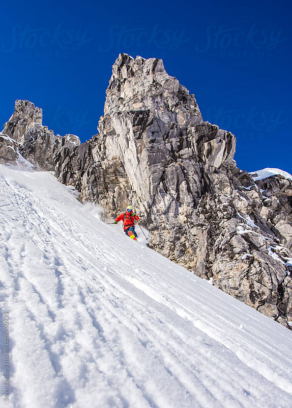 Skier skiing steep rocky mountain snow by Soren Egeberg for Stocksy United