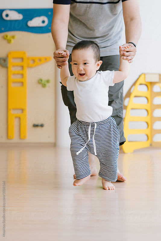 Toddler boy learning to walk with his father helping him by MaaHoo Studio for Stocksy United