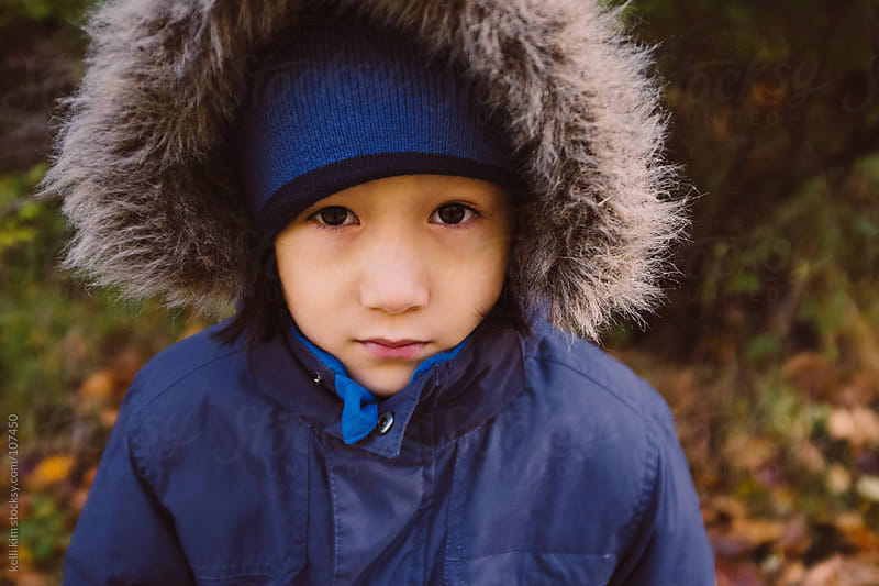 Closeup of serious child's face in fur lined hood  by Kelli Seeger Kim for Stocksy United