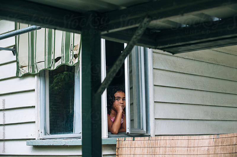 Girl looks out window. by Shannon Aston for Stocksy United