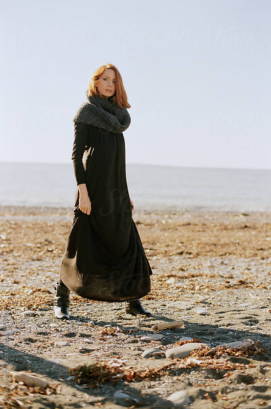 Woman standing on the seashore in sunny autumn day by Lyuba Burakova for Stocksy United