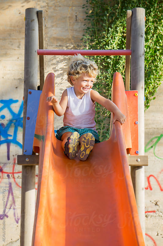 Blond boy in an orange slide by ACALU Studio for Stocksy United