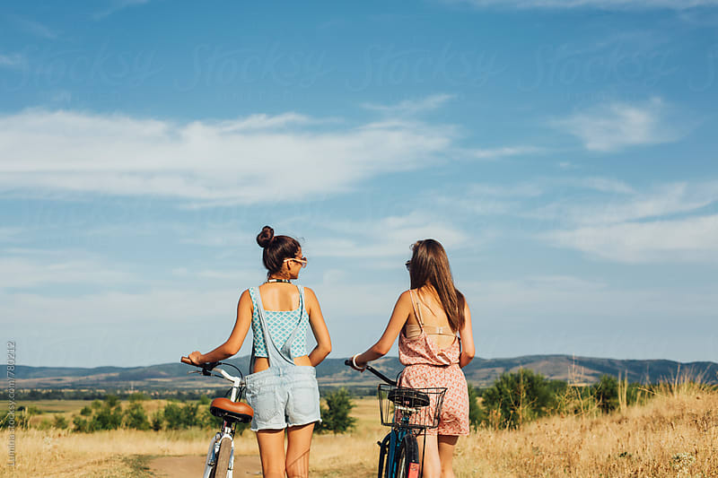 Two Girlfriends Riding Bicycles Together by Lumina for Stocksy United