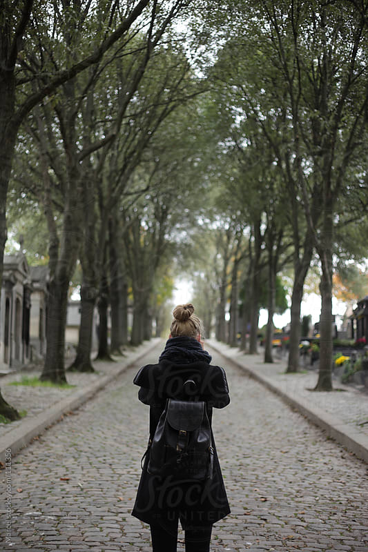 Young woman taking a photo at a famous graveyard in Paris by Marcel for Stocksy United