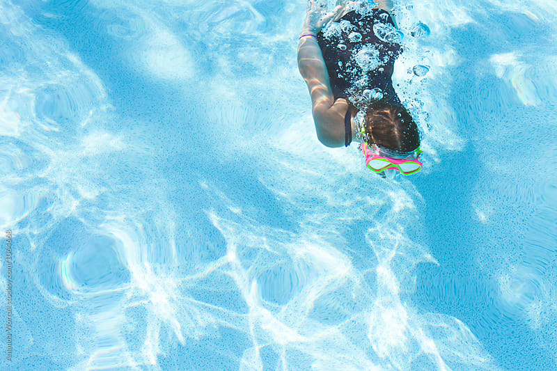 A girl swimming underwater in a pool by Amanda Worrall for Stocksy United