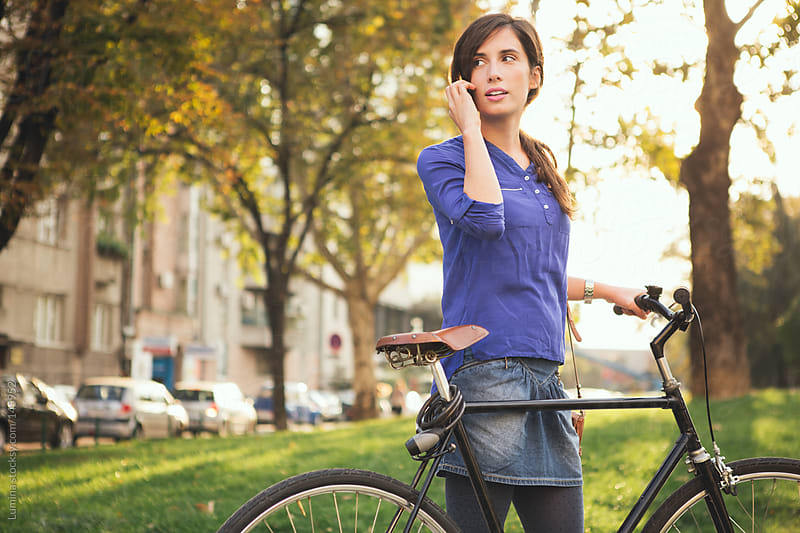 Woman With Bike Telephoning by Lumina for Stocksy United