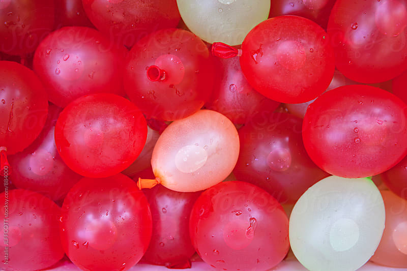 Bright coloured water balloons filled and ready for fight by Natalie JEFFCOTT for Stocksy United