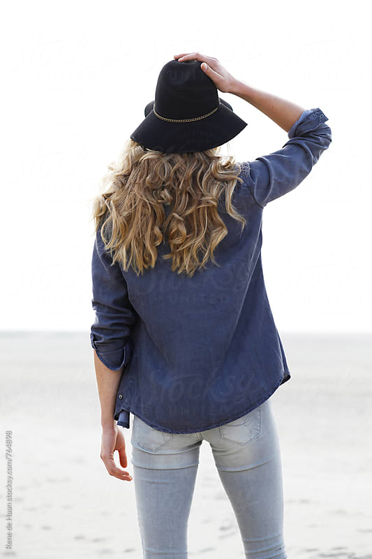 woman with hat and blonde hair, from the back, looking in distance by Rene de Haan for Stocksy United