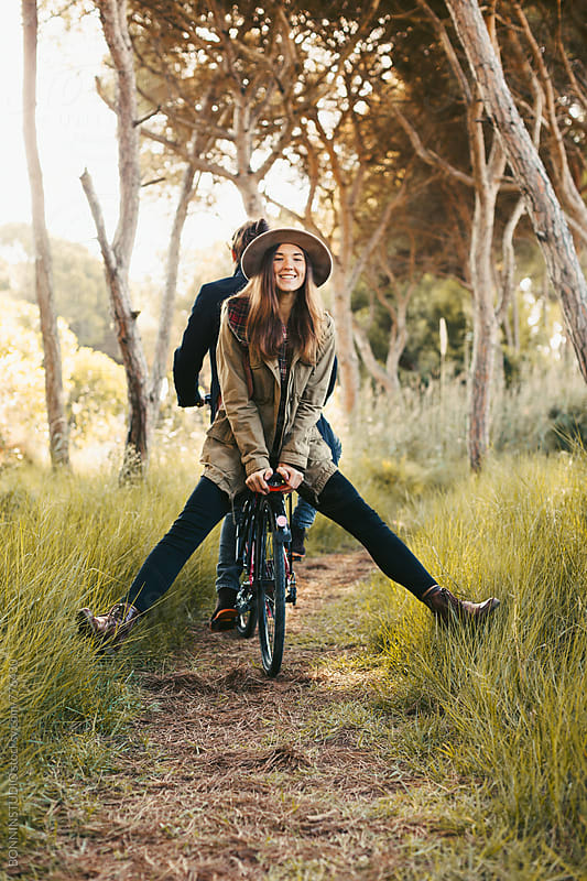 Portrait of a woman having fun with her boyfriend on a bicycle. by BONNINSTUDIO for Stocksy United