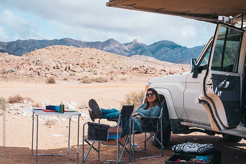 woman relaxing in the shade of a car awning on a desert road trip by Micky Wiswedel for Stocksy United