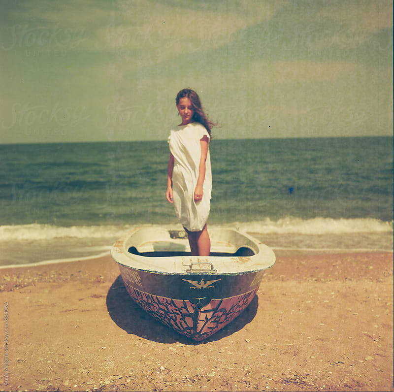 A film portrait of young woman standing in the boat at the seashore by Anna Malgina for Stocksy United