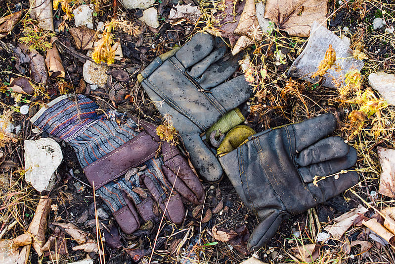 Old work gloves on the ground  by Pixel Stories for Stocksy United
