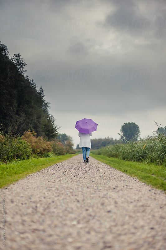 Woman from the back holding a purple umbrella walking on a stone path by Cindy Prins for Stocksy United