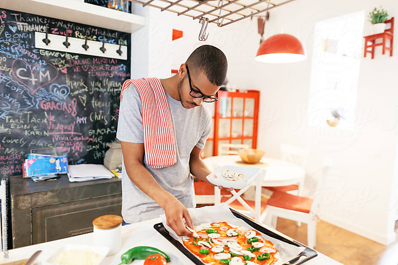 Latin man making homemade vegetable pizza at home. by BONNINSTUDIO for Stocksy United