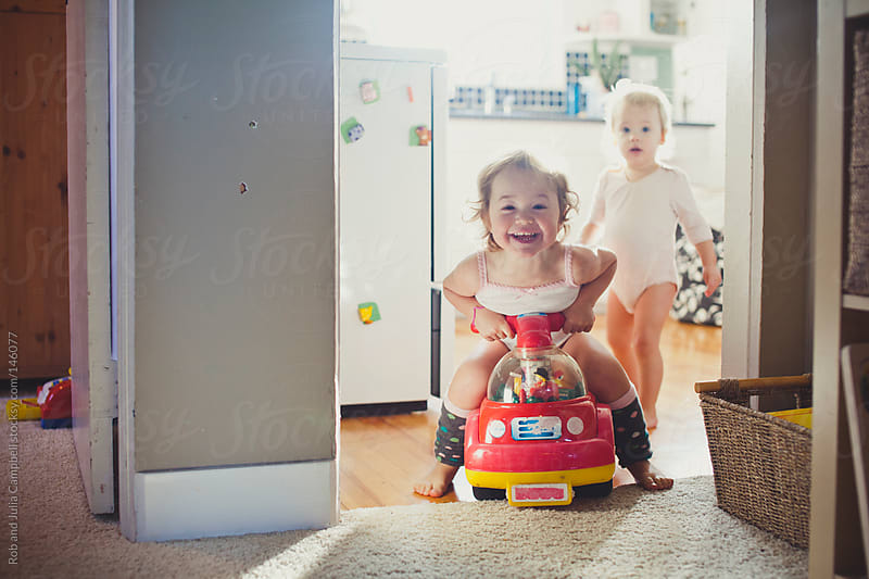 Toddler girl riding toy car having fun by Rob and Julia Campbell for Stocksy United