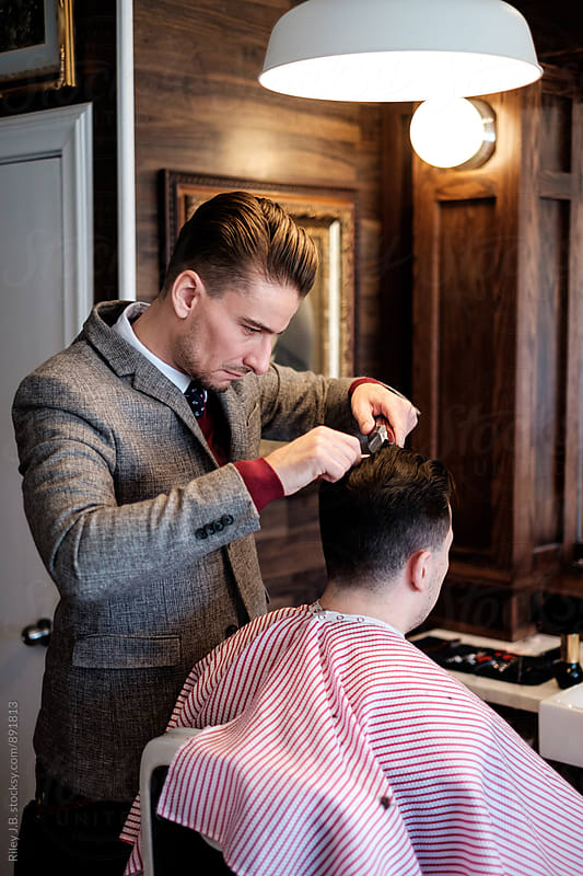 A gentleman barber focuses intently while cutting a client's hair. by Riley J.B. for Stocksy United