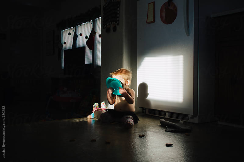 Toddler holding bowl in face sitting in sunlight  by Jessica Byrum for Stocksy United