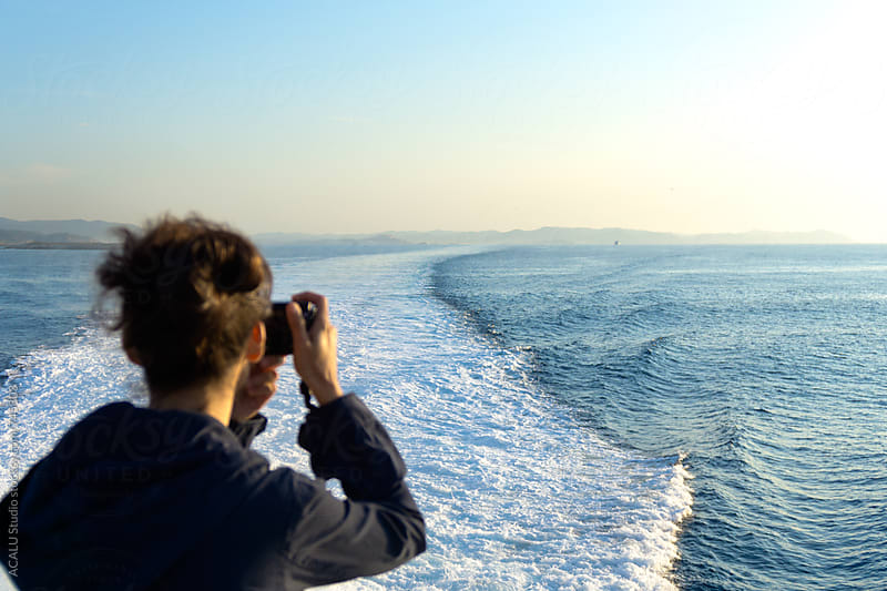 Woman photographing the wake of a boat by ACALU Studio for Stocksy United
