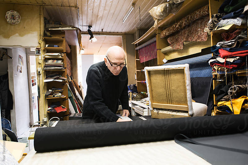 Senior working in his textile store by Ivar Teunissen for Stocksy United