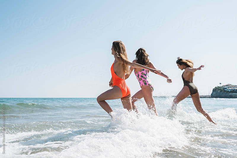 Happy friends having fun in the sea by Simone Becchetti for Stocksy United