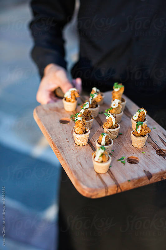 Servers's hands holding food at event by Andrew Cebulka for Stocksy United