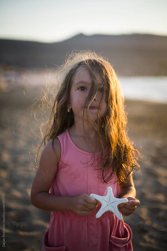 Child holding starfish on the beach by Dejan Ristovski for Stocksy United