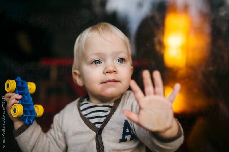 toddler boy holding a car and looking happily out throw a glass pane by Amanda Voelker for Stocksy United