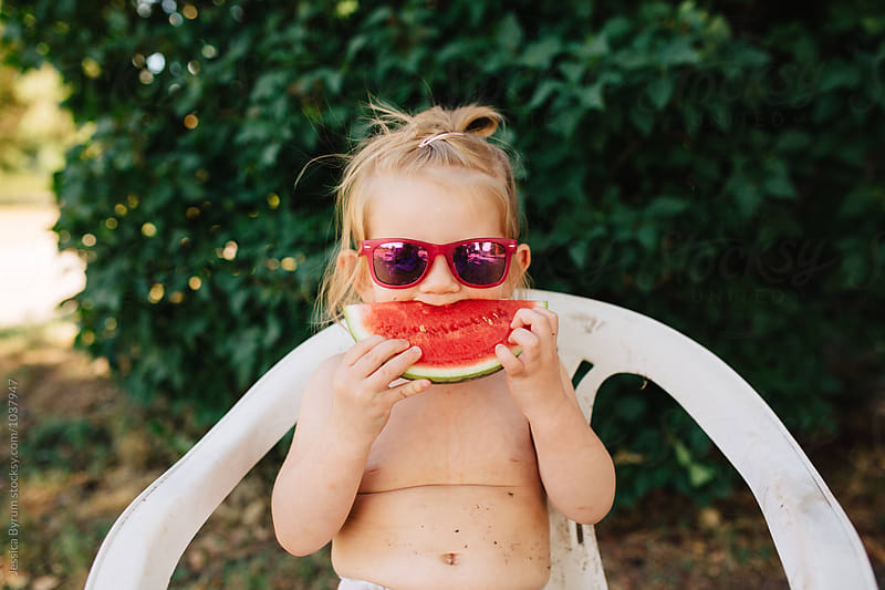 Cute toddler girl eating watermelon outside in the summer. by Jessica Byrum for Stocksy United