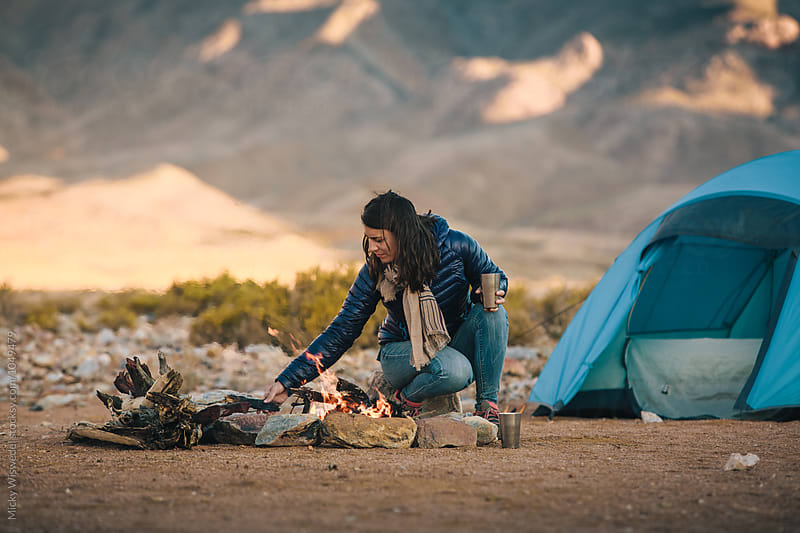 Hiker making a camp fire outside her tent in the mountains by Micky Wiswedel for Stocksy United