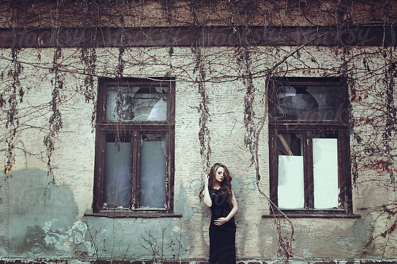 Girl standing in front of abandoned house by Jovana Rikalo for Stocksy United