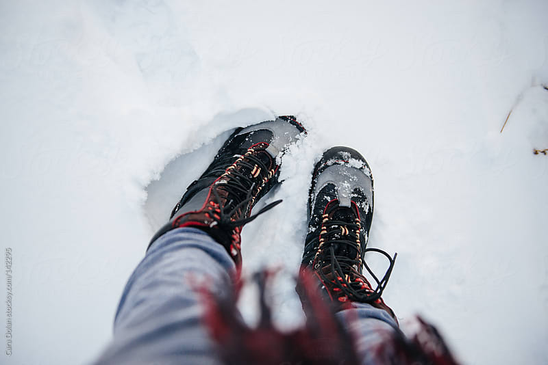 Looking down at a woman's feet in the snow by Cara Dolan for Stocksy United