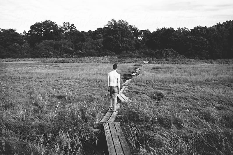 Young man walking down a path by Joe St.Pierre Photography for Stocksy United