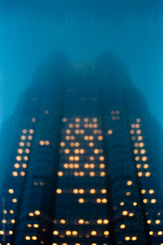 Out of focus office tower on a foggy night by Riley Joseph for Stocksy United