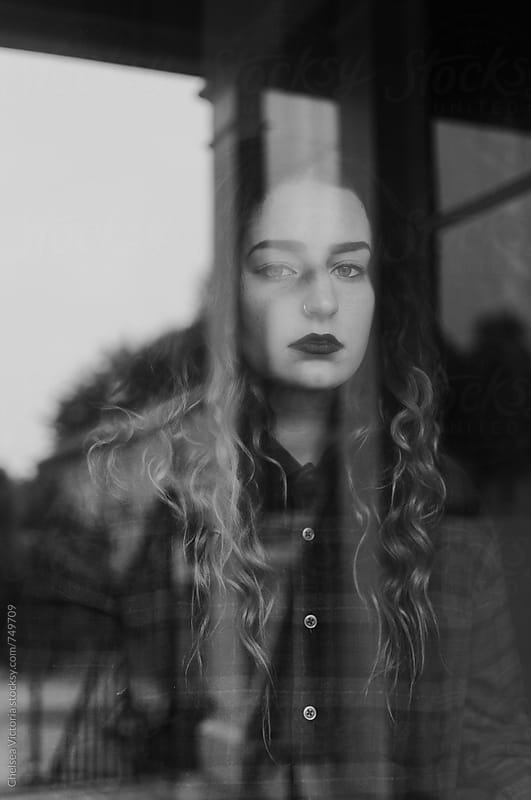 A young woman staring out of the window by Chelsea Victoria for Stocksy United