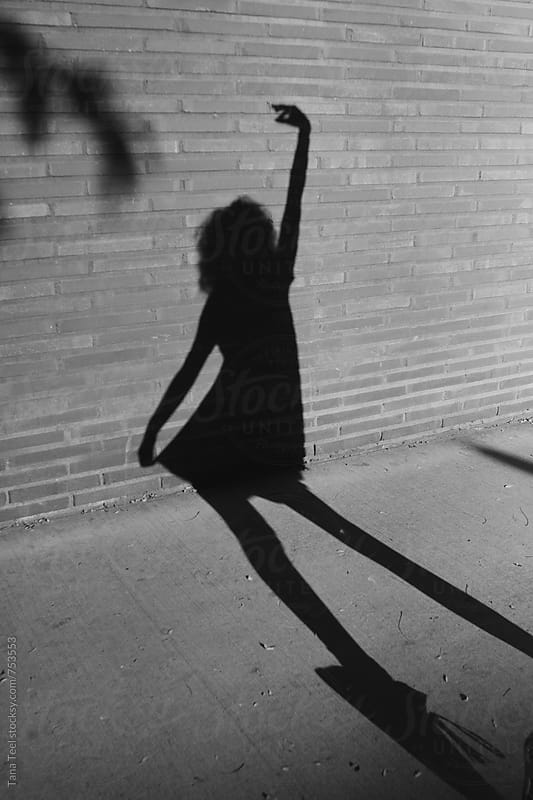 Shadow of female in dress falls on brick wall of building by Tana Teel for Stocksy United
