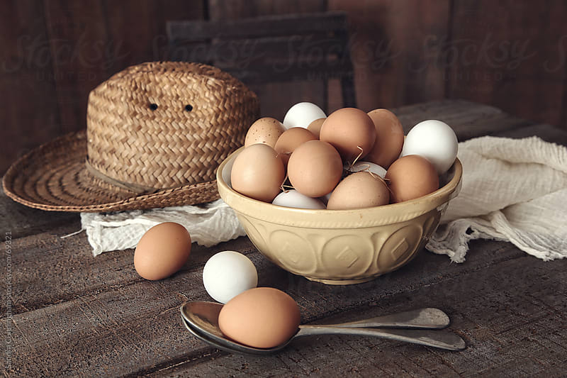 Bowl of fresh country eggs on rustic table by Sandra Cunningham for Stocksy United