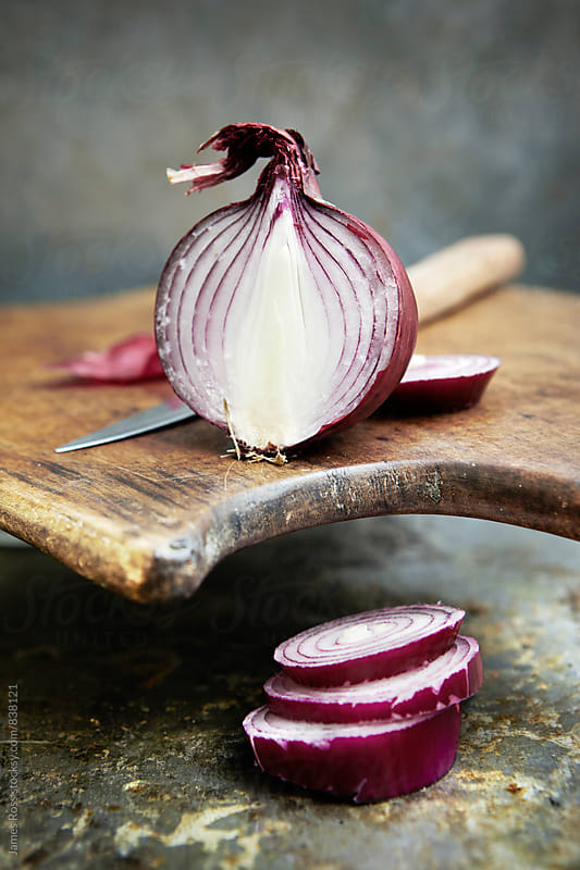 Red onions on a wooden chopping board by James Ross for Stocksy United