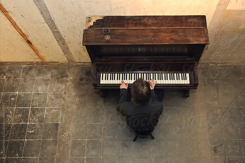 Bird's eye view of pianist playing old piano by Urs Siedentop & Co for Stocksy United