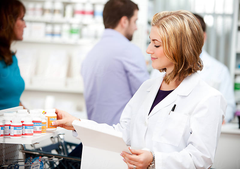 Pharmacy: Pharmacist Putting Out More Medicine on Shelf by Sean Locke for Stocksy United