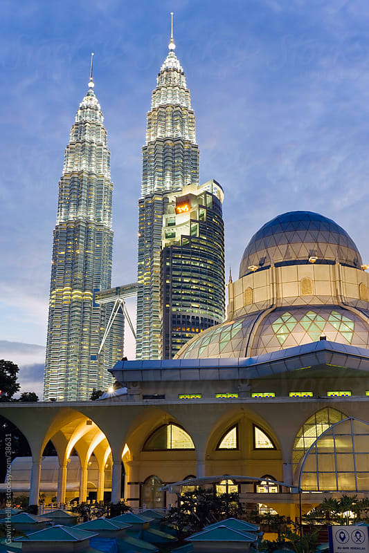 Asia, Malaysia, Selangor State, Kuala Lumpur, Mosque in the KLCC city park grounds at the base of the iconic Petronas Towers, 88 storey steel clad twin towers with a height of 451.9 metres - illuminated at dusk by Gavin Hellier for Stocksy United