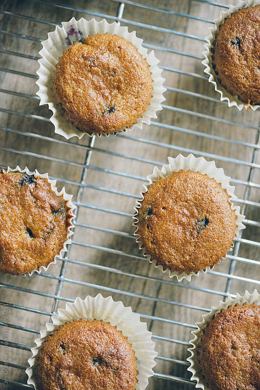 Muffins on a cooling rack straight out of the oven by Jen Grantham for Stocksy United