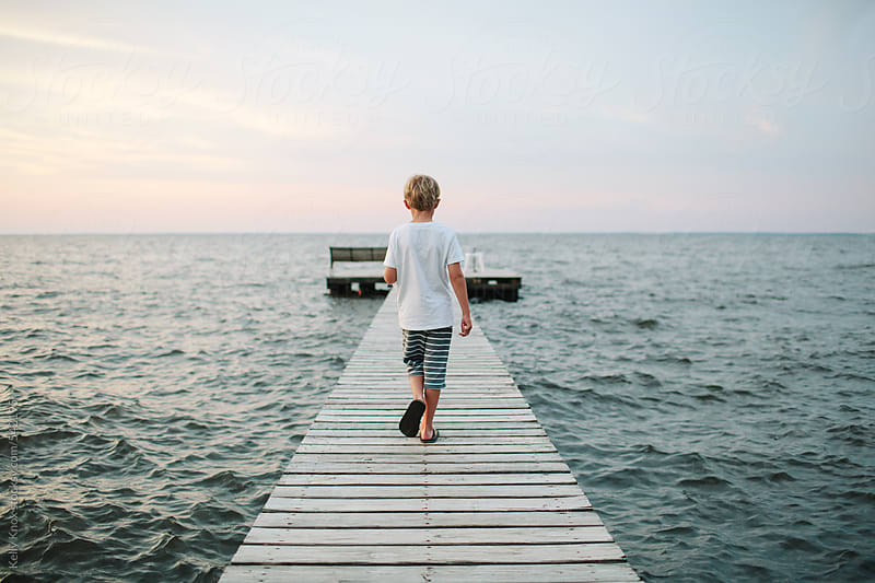 boy walking down a pier at sunset by Kelly Knox for Stocksy United