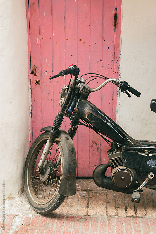 An old motorcycle parked against a pink door by Maresa Smith for Stocksy United