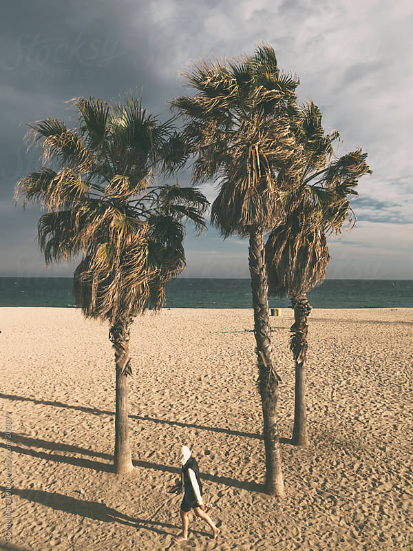 Man walking on the beach sand. Three palm tree background.  by BONNINSTUDIO for Stocksy United