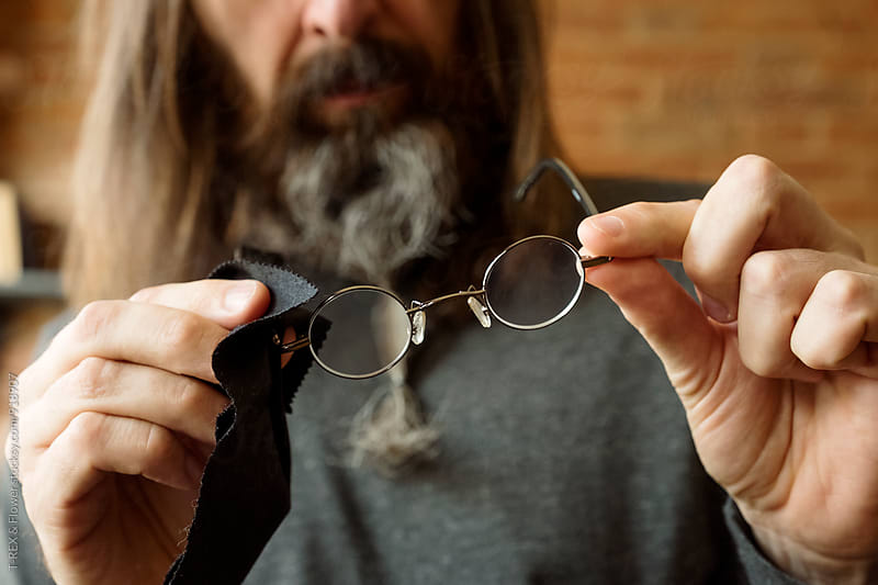 Man checking how clean his eyeglasses are by T-REX & Flower for Stocksy United