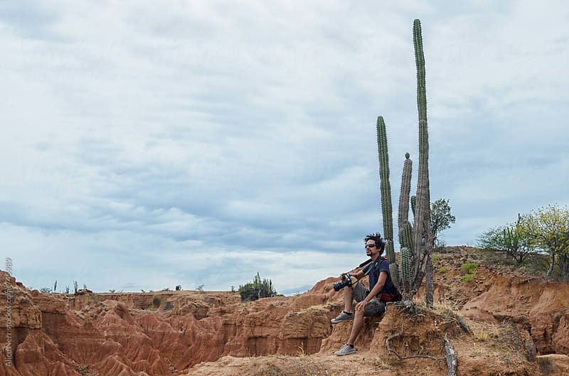 Travel photographer sitting next to the cactus above sandstone canyon by Alice Nerr for Stocksy United