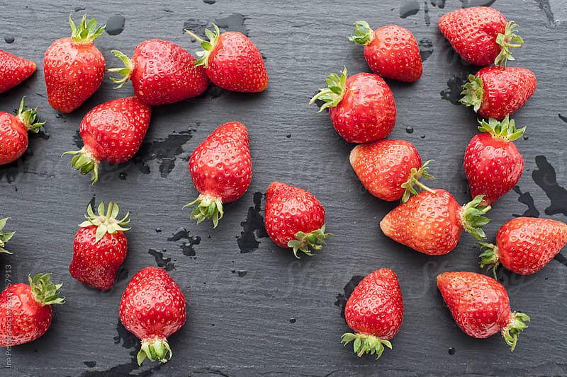 Food: Strawberries on slate  by Ina Peters for Stocksy United