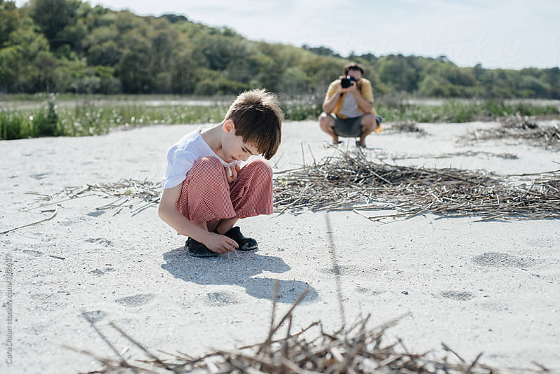 Father takes a photo of his son playing on a beach by Cara Dolan for Stocksy United