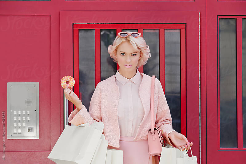 Pink Shopping Lady with doughnut by Aila Images for Stocksy United