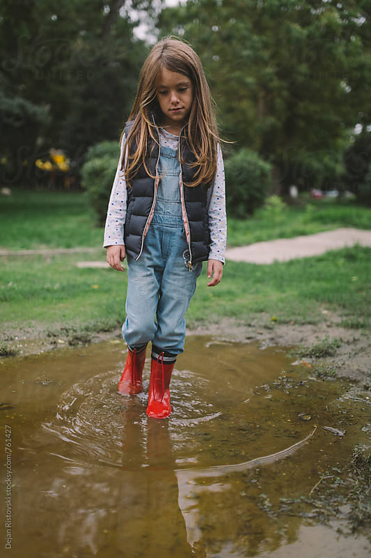 Child walking in water after rain by Dejan Ristovski for Stocksy United